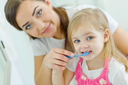 Mom and Daughter brushing their teeth - Pediatric Dentist in Columbus, GA